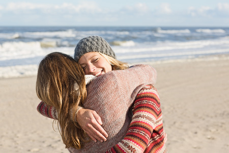 Smiling women hugging on beach