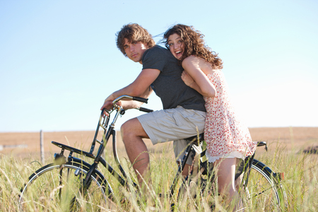 in twos: Couple riding bicycle in tall grass