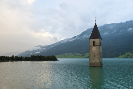 Clock tower submerged in rural lake