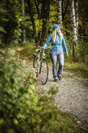 Woman walking bicycle in park LANG_EVOIMAGES
