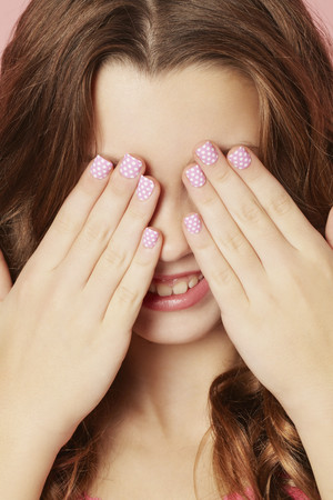 bashfulness: Smiling girl with polka dot manicure LANG_EVOIMAGES