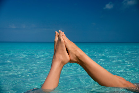 Feet touching in tropical water LANG_EVOIMAGES