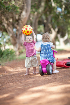 Toddlers playing together on dirt road