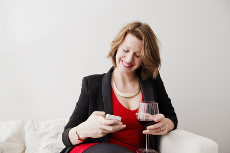 gratify: Woman with wine using cell phone