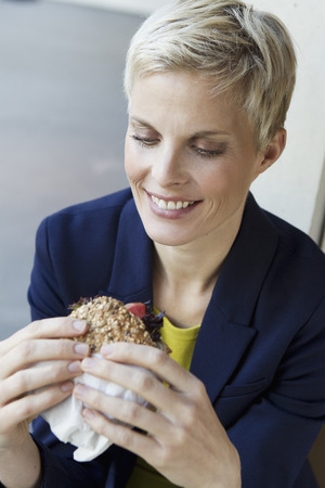 nourishing: Smiling woman eating sandwich LANG_EVOIMAGES