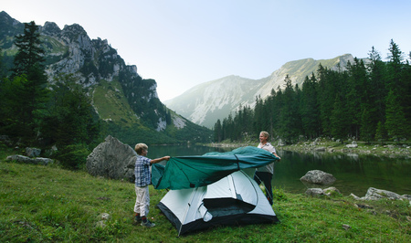 Father and son pitching tent together LANG_EVOIMAGES