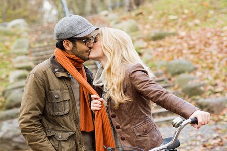 smooching: Couple kissing in park LANG_EVOIMAGES