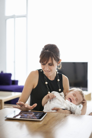 cries: Businesswoman holding crying son LANG_EVOIMAGES