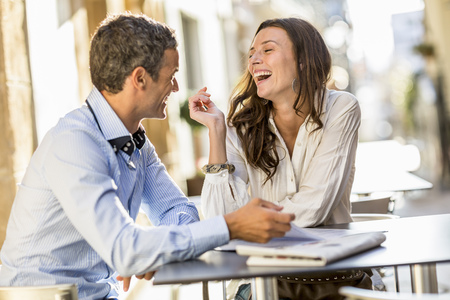 enthusiastically: Couple laughing at sidewalk cafe