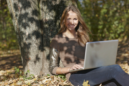 shadowed: Woman using laptop in autumn leaves