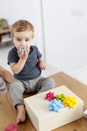 Toddler boy sitting with birthday present
