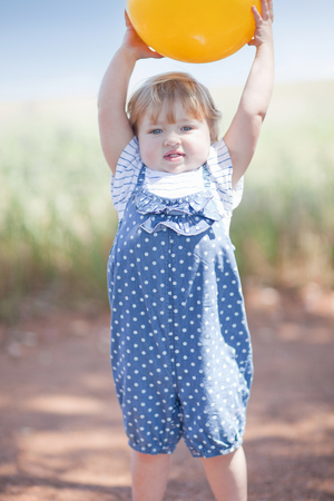 Toddler girl with ball on dirt road