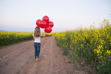 Girl carrying balloons on dirt road LANG_EVOIMAGES
