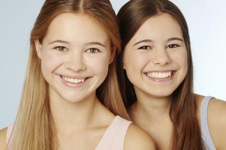 Teenage girls smiling together LANG_EVOIMAGES