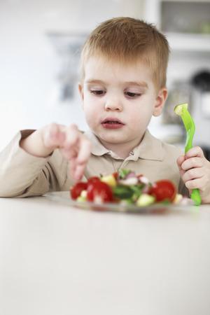 close up food: Boy picking at plate of fruit in kitchen LANG_EVOIMAGES
