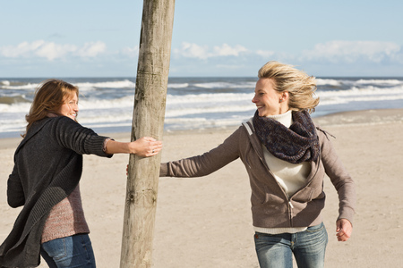 pursued: Smiling women playing on beach