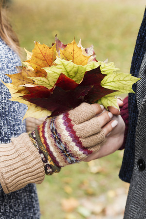 Close up of couple holding autumn leaves