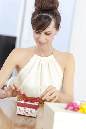 Woman unwrapping present at table LANG_EVOIMAGES