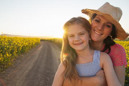Mutter und Tochter, die auf Schotterweg umarmen LANG_EVOIMAGES