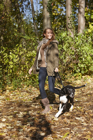 Woman walking dog in forest