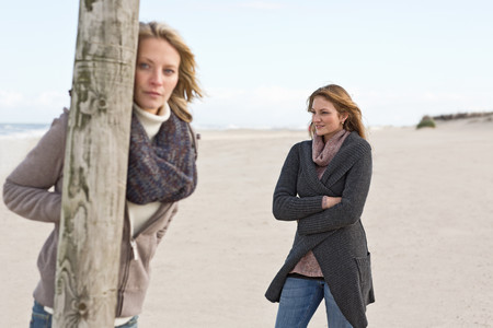 somber: Women standing on beach