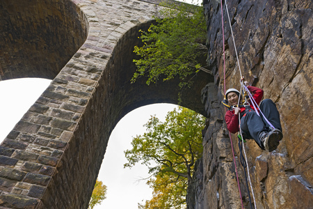 jeopardizing: Rock climber scaling brick wall LANG_EVOIMAGES