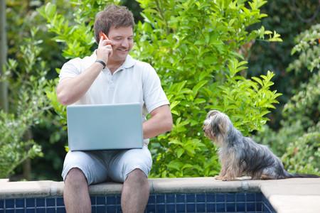 reconocimientos: Hombre que usa el teléfono celular y la computadora portátil al aire libre LANG_EVOIMAGES