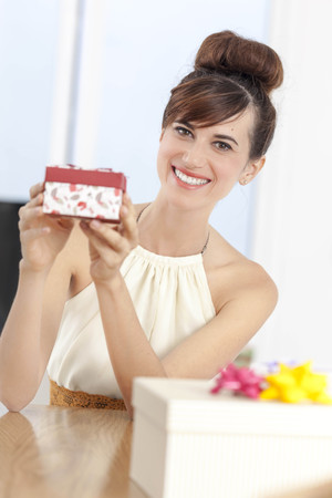 Woman holding present at table