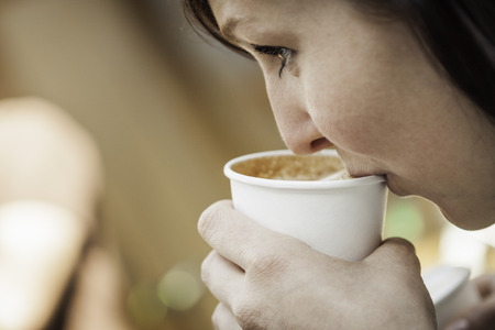 Close up of woman drinking cup of coffee