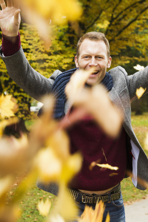 tosses: Man playing in autumn leaves