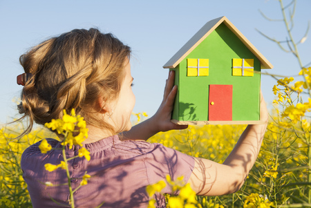 advances: Girl holding model house in field