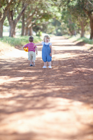 motioning: Toddlers playing on dirt road