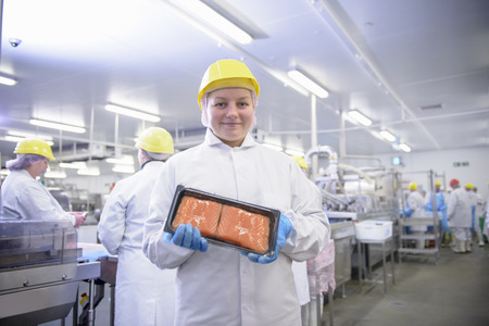 worked: Worker holding packed fish in factory
