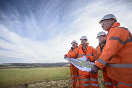 Workers reading blueprints in field