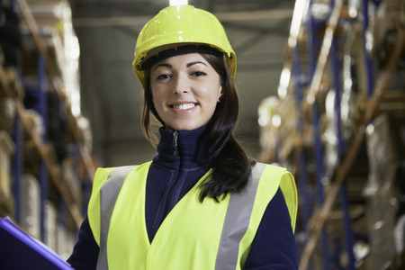 industrialization: Smiling worker standing in warehouse LANG_EVOIMAGES