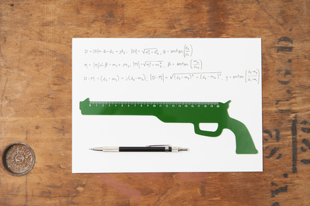 cautions: Gun shaped ruler and pen on paper
