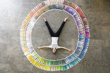 conferring: Businessman laying in paint swatches LANG_EVOIMAGES