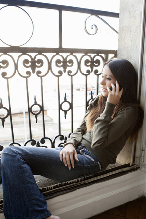 responding: Woman on cell phone in windowsill