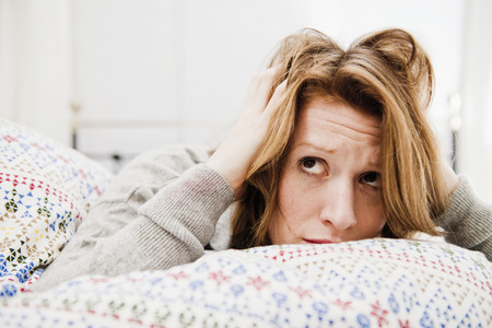 Woman ruffling her hair on bed