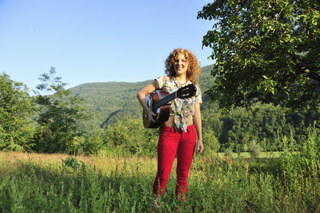Woman holding guitar in grassy field