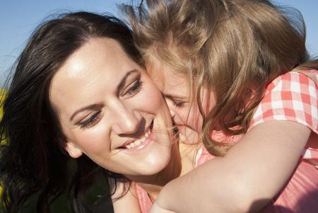 curare teneramente: Madre e figlia che abbracciano all'aperto LANG_EVOIMAGES
