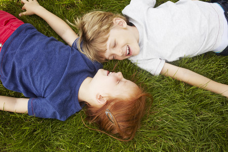 talker: Smiling children laying in grass together