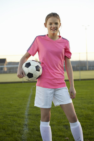 preadolescent: Football player holding ball in field LANG_EVOIMAGES