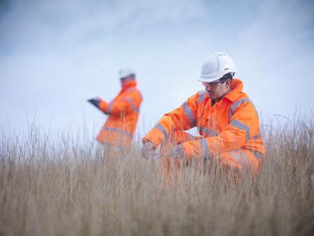 agachado: Ecologistas examinando hierba alta