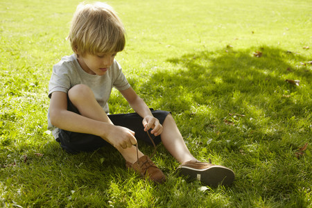 tied down: Boy tying his shoe in grass