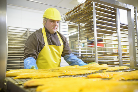 hard: Worker examining smoked fish in factory