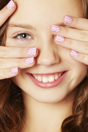 peep: Smiling girl with polka dot manicure LANG_EVOIMAGES