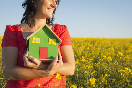 Woman holding model house in field