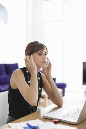通信: Businesswoman talking on cell phone LANG_EVOIMAGES