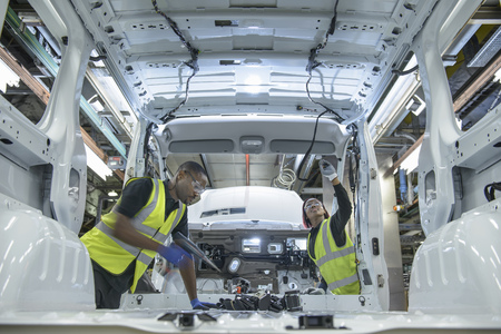 leaning on the truck: Workers fitting parts in car factory